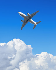 Wall Mural - Airplane flying in the blue sky with clouds