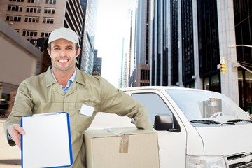 Composite image of happy delivery man with box showing clipboard