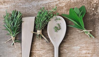 herbes aromatiques et cuillère en bois sur planche