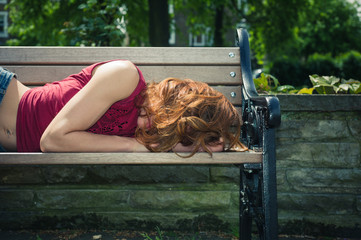 Young woman relaxing on park bench