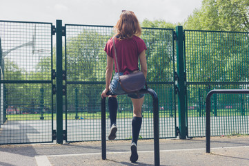 Young woman sitting on a rail in park