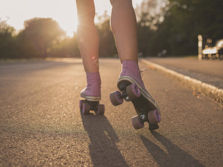 Legs of young woman roller skating in park
