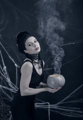 Halloween. Молодая ведьма с волшебным напитком