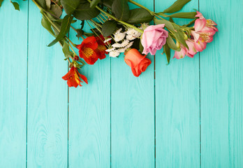 Frame of flowers on blue wooden background.