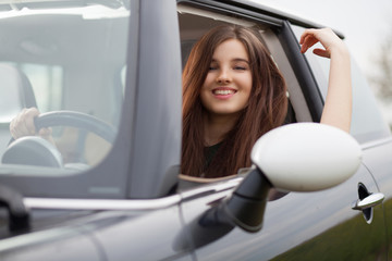 Young beuatiful woman driving a car