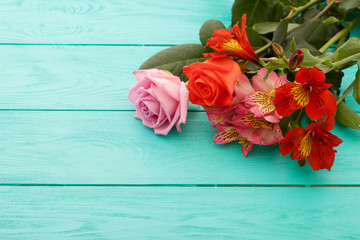 Fresh flowers on blue wooden background. Place for text. Selective focus