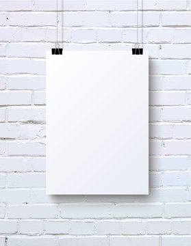 White vertical blank piece of paper on the white brick wall