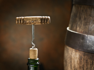 Opening of a wine bottle with corkscrew.