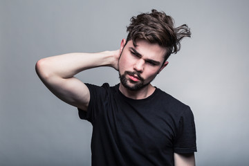 Young man in black t-shirt holds head in his hands