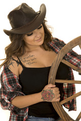 cowgirl with tattoos wagon wheel look at wheel