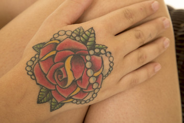 tattoo of rose on hand by leg