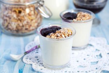 Small jar with homemade yogurt with blackcurrant jam and granola