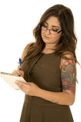 woman in brown dress tattoos writing on clipboard