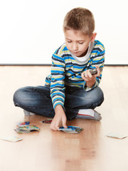 Child boy playing cards on floor