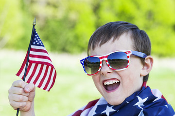 4th of july holiday: happy boy in sunglasses holding  American flag