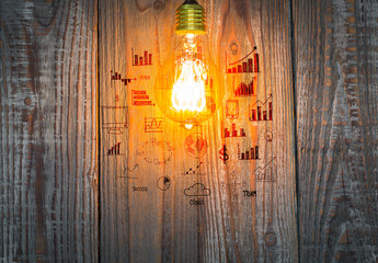 Glowing bulb with drawing graph on the wood background