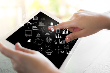 Woman hand hold white tablet with graph and chart symbols