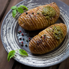 Hasselback potatoes with sea salt, pepper and pesto, close-up