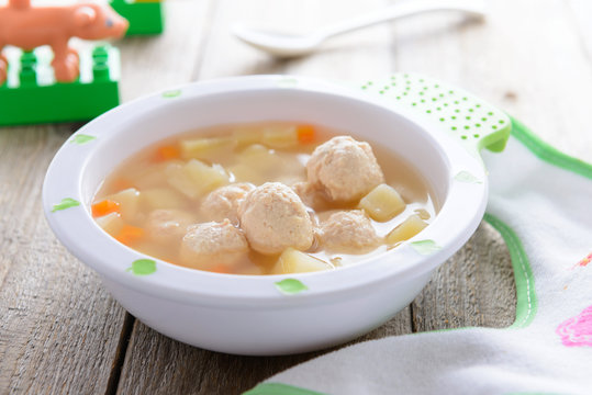 Child food: soup with potatoes and chicken meatballs
