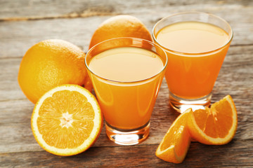 Glass of fresh orange juice on grey wooden background