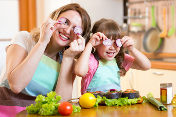 mother and daughter playing with vegetables in kitchen, healthy