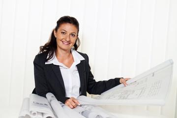 Architekt mit Bauplan im Büro.