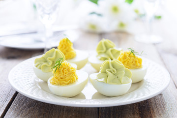 Eggs stuffed with cheese and avocado mousse on festive table