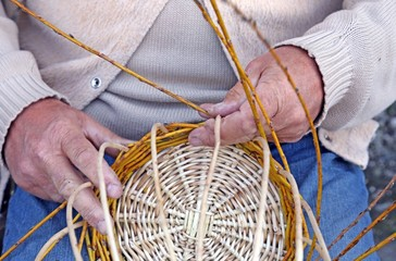 hands of elder craftsmen create a woven wicker basket
