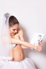 Bride in a veil, underwear and skirt tears a photo of her groom