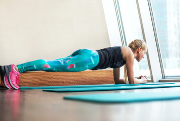 Blonde female doing plank static exercise in gym