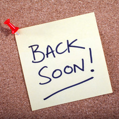 A 'Back Soon' note pinned on a noticeboard.