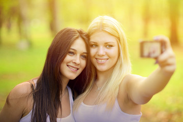 Outdoor portrait of two girl friends taking photos with camera