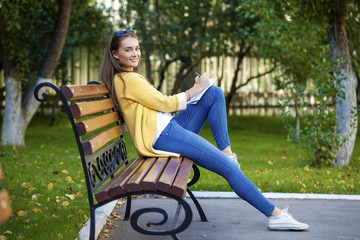Happy young brunette sitting on a park bench