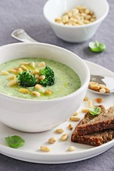 Broccoli-potato soup with pine nuts and broccoli topping