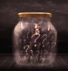 Businessman locked into a jar with question marks concept