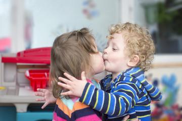 Little boy kiss a little girl