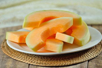 cantaloupe melon slices  on white plate