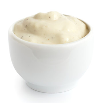 Small pot of garlic mayonnaise dressing, isolated, detail.