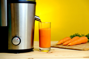 Juicer and carrot juice in glass on yellow background