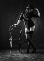 Sexy woman in black stockings and hat is dancing around a chair