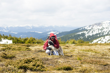 hiker playing with puppy in mountains