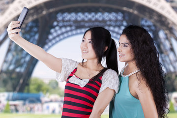Two girls taking photos at Eiffel Tower