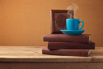 Coffee cup and books on wooden vintage table
