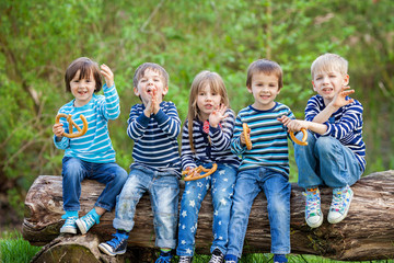 Five adorable kids, dressed in striped shirts, sitting on wooden