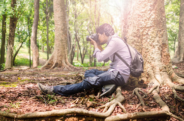 Photographer taking photos  using DSLR camera in nature