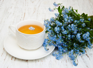 Cup of teand forget me not flowers