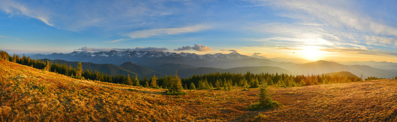Panoramic view of mountain range and sunset meadow