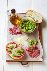 Italian snacks. salami sandwich with parmesan cheese & broad bea