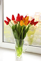 Bouquet of fresh tulips on windowsill background