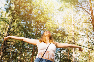 Relaxed boho woman with raised hands feeling free outdoors